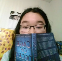 Photo of Sophia with a book covering half of her face
