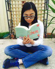 Photo of Stephanie reading Fangirl outdoors